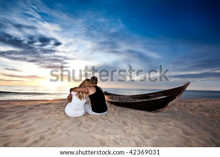 Romantic couple and boat on the beach at sunrise time - stock photo