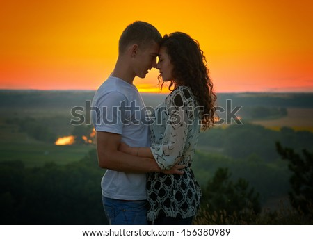 romantic couple at sunset on bright yellow sky background, love tenderness concept, young adult people - stock photo