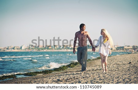 Romantic couple at the beach walking together. - stock photo