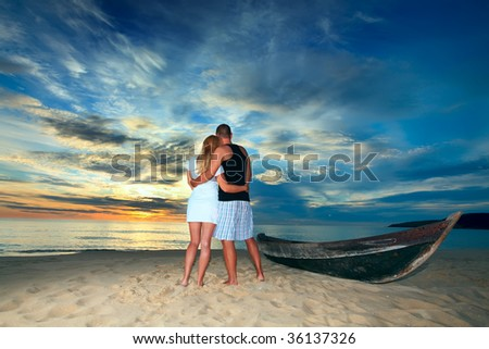 Romantic couple at uninhabited island at sunset time - stock photo