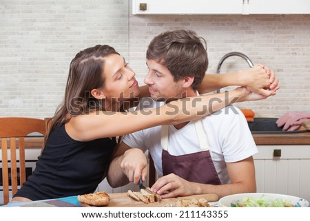 Romantic couple cooking together at the kitchen - stock photo