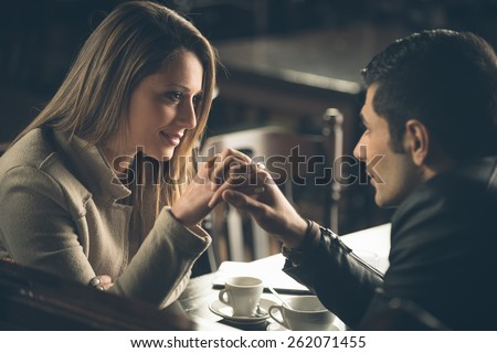 Romantic couple dating at the bar with hands clasped - stock photo