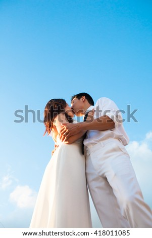 Romantic couple dressed in white, kissing under the blue sky on their wedding day. - stock photo