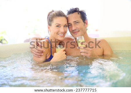 Romantic couple drinking cahmpagne in hot tub - stock photo