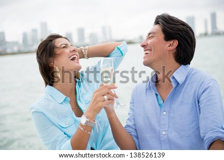 Romantic couple drinking champagne on a boat - stock photo