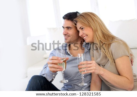 Romantic couple drinking wine at home - stock photo