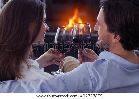 Romantic couple drinking wine at home near fireplace