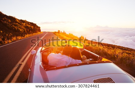 Romantic Couple Driving into the Sunset in Classic Vintage Sports Car - stock photo