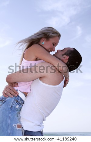 Romantic couple embracing at seaside on a blue sky background