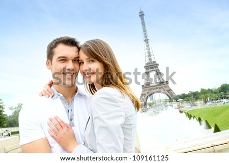 Romantic couple embracing in front of the Eiffel tower - stock photo