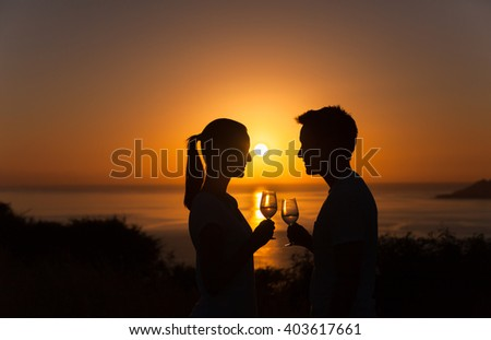 Romantic couple enjoying a glass of wine and beautiful sunset view.  - stock photo
