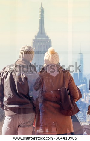 Romantic couple enjoying in New York City panoramic view. Manhattan downtown skyline with illuminated Empire State Building and skyscrapers seen from observation deck terrace.  - stock photo