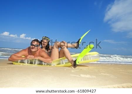 Romantic couple enjoying on an inflatable beach mattress - stock photo