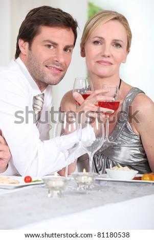 Romantic couple enjoying rose wine with dinner - stock photo