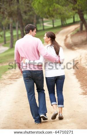 Romantic couple enjoying walk in park - stock photo