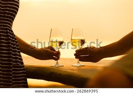 Romantic couple enjoying wine by the sea - stock photo