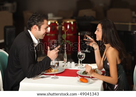Romantic couple having dinner, smiling to each other - stock photo