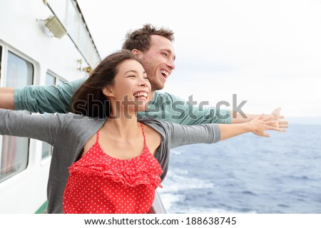 Romantic couple having fun laughing in funny pose on cruise ship boat. Smiling happy man and woman on travel vacation holidays on open ocean sea. - stock photo