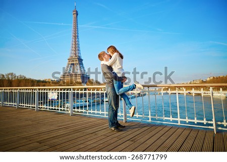 Romantic couple having fun near the Eiffel tower and kissing - stock photo