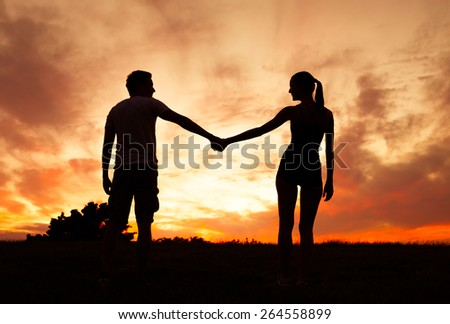 Romantic couple holding hands and enjoying each others company. - stock photo