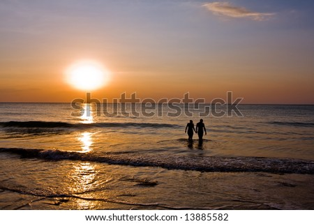 romantic couple holding hands in the ocean at sunset - stock photo