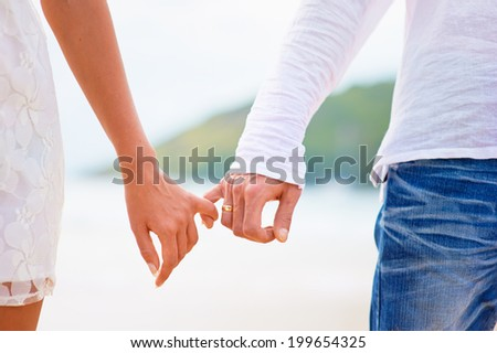 Romantic couple holding hands on a beach in sunset. - stock photo