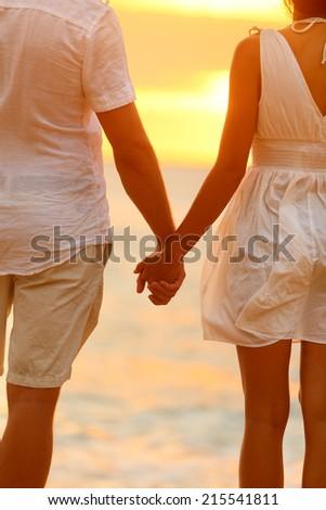 Romantic couple holding hands on beach sunset during travel. Happy woman and man in romance on honeymoon romance in beautiful sun light. - stock photo