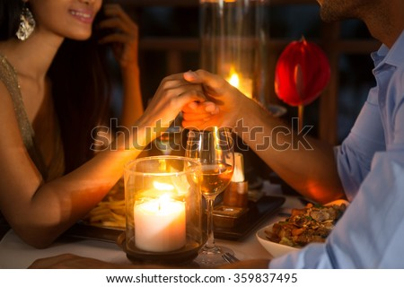 Romantic couple holding hands together over candlelight during romantic dinner  - stock photo