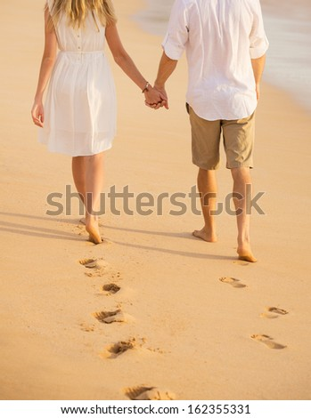 Romantic couple holding hands walking on beach at sunset. Man and woman in love. Footprints in the sand.  - stock photo
