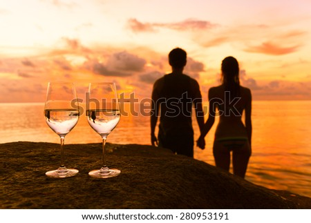 Romantic couple holding hands while watching the sunset. - stock photo