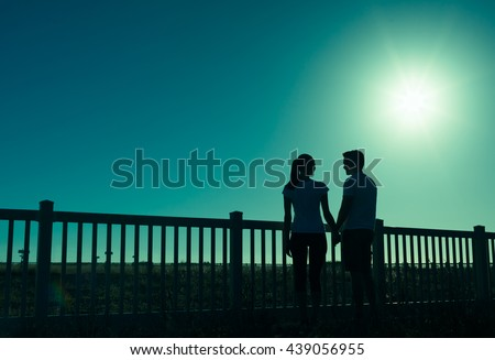 Romantic couple holding hands with a full moon glowing in the distance.  - stock photo