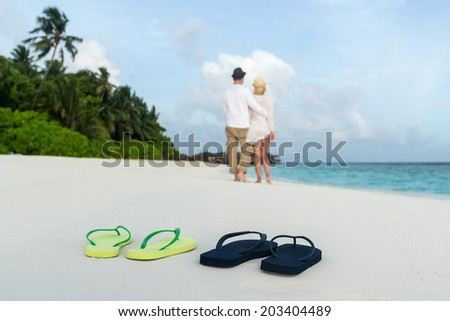 romantic couple hug on sea sand beach against male and female flip flops closeup - stock photo