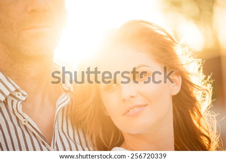 Romantic couple hugging outdoor - photographed at sunset against direct sun - stock photo