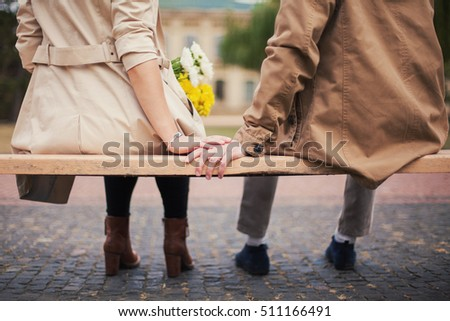 Romantic couple in beige coat sitting on a bench holding hands together. Hand touch, girl with flowers