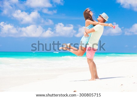 Romantic couple in bright clothes enjoying sunny day at tropical beach - stock photo