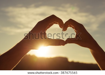 Romantic couple in love gesturing a heart with fingers on the sunset - stock photo
