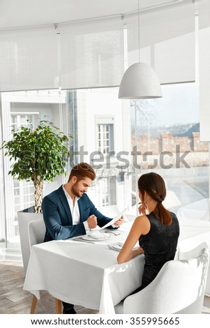 Romantic Couple In Love Having Dinner In Luxury Gourmet Restaurant. Happy Beautiful Lovely People Reading Menu, Choosing Food, Celebrating Anniversary Or Valentine's Day. Romance And Relationships.