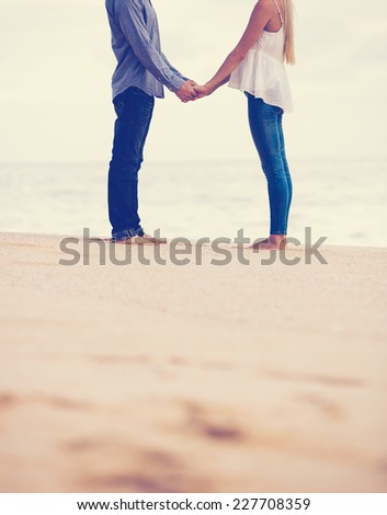 Romantic Couple in Love Holding Hands on the Beach at Sunset - stock photo