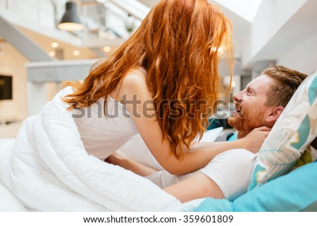 Romantic couple in love lying on bed and being passionate