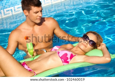 Romantic couple in outdoor pool at summertime. - stock photo