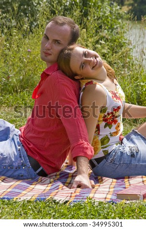 Romantic couple is sitting on the plaid. Portrait of a happy couple at the park on vacation. Charming young girl and boy spending quality time. - stock photo