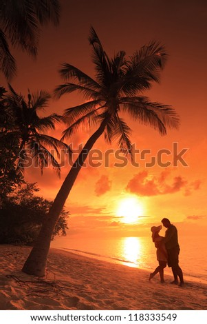 Romantic couple kissing at beach with sunset in the background at Kuredu island, Maldives, Lhaviyani atoll - stock photo