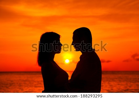 Romantic couple kissing at tropical beach with sunset in the background - stock photo