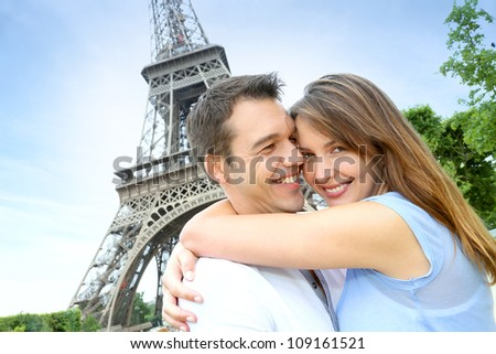 Romantic couple kissing by the Eiffel Tower - stock photo