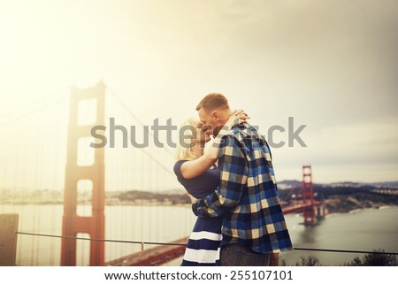 romantic couple kissing in front of golden gate bridge with lens flare and retro image filter with warm tones - stock photo