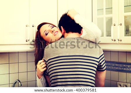 Romantic couple kissing in the kitchen. - stock photo