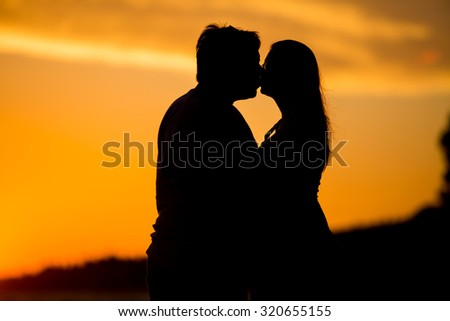 Romantic couple kissing on the beach at colorful sunset on background