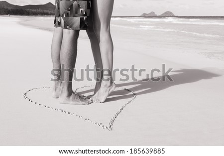 Romantic couple kissing on the beach. Love - male and female feet in the heart on the beach. Black and white image.  - stock photo