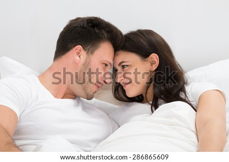 Romantic Couple Looking At Each Other Lying On Bed - stock photo