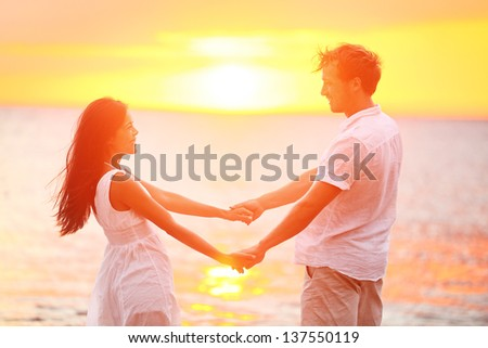 Romantic couple lovers holding hands at beach sunset. Happy multiethnic young couple in love having romance and fun together during summer travel beach vacation. Asian woman, Caucasian man in sun. - stock photo